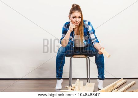 Worried helpless woman assembling wooden furniture. DIY enthusiast. Young girl doing home improvement. poster