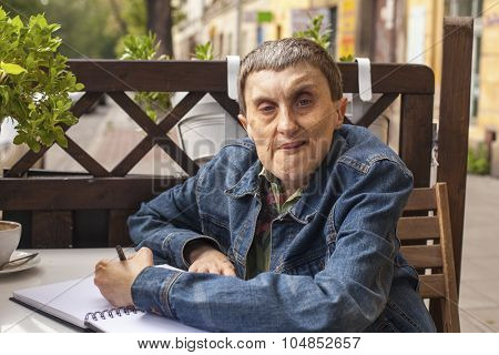Adult disabled man with cerebral palsy sitting with a notebook at an outdoor cafe.