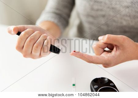medicine, diabetes, glycemia, health care and people concept - close up of woman checking blood sugar level by glucometer at home poster