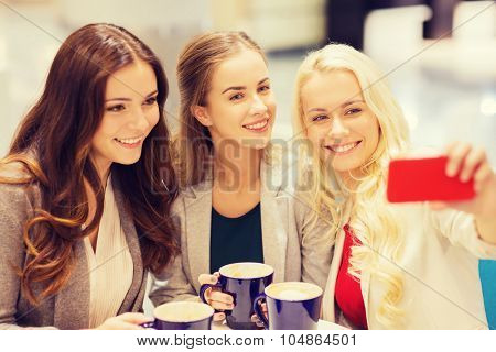 drinks, friendship, technology and people concept - happy young women with cups sitting at table and taking selfie with smartphone in cafe
