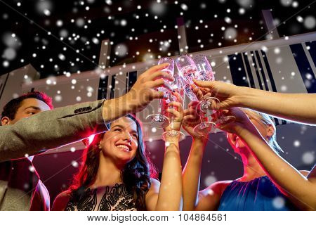 party, holidays, celebration, nightlife and people concept - smiling friends with glasses of non-alcoholic champagne in club