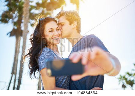 man kissing his girlfriend on the cheek for romantic selfie with lens flare and palm trees in background shot with extremely thin depth of field and lens flare effect poster