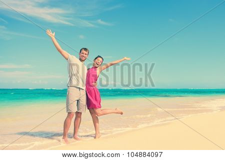 Full length portrait of happy couple with arms raised standing on shore. Joyful partners are enjoying at beach. Carefree tourists are celebrating summer vacation in idyllic nature.