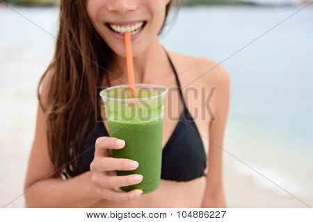 Green smoothie. Woman holding green vegetable detox juice outside in bikini in summer sun on beach. Healthy lifestyle with beautiful mixed race Asian Caucasian female model taking a cleanse diet.