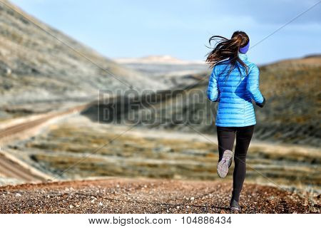 Woman winter and autumn running in down jacket. Female running jogging on mountain trail in beautiful landscape. poster