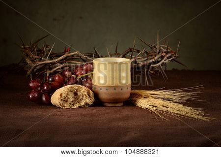 Communion concept with cup of wine, bread, crown of thorns, red grapes and wheat on table