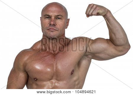 Portrait of muscular man flexing bicep against white background