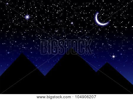 Nights sky over the pyramids in Egypt with a crescent moon