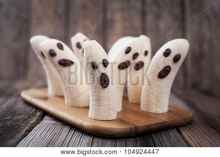 Homemade halloween scary banana ghosts monsters with chocolate faces. Healthy natural vegetarian sna