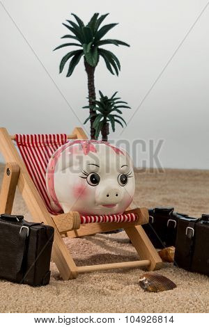 a piggy bank is in a deckchair. symbolic photo for travel and cheap cost holiday