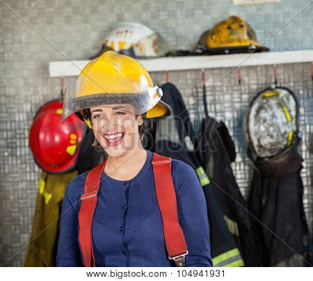 Cheerful firewoman looking away while standing at fire station