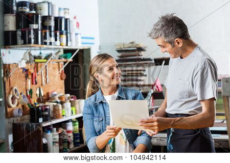 Happy male and female worker looking at each other while holding paper in factory
