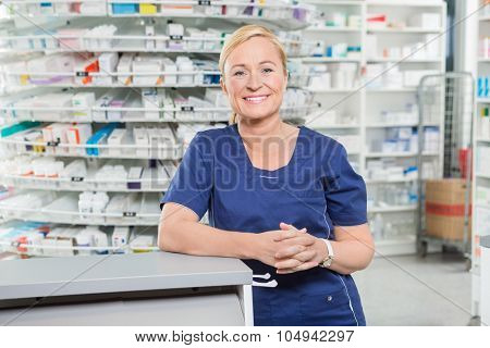 Portrait of confident female chemist leaning at cash counter in pharmacy