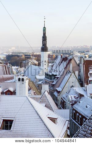 Cityscape of the old town of Tallinn with snowy rooftop and city hall spire