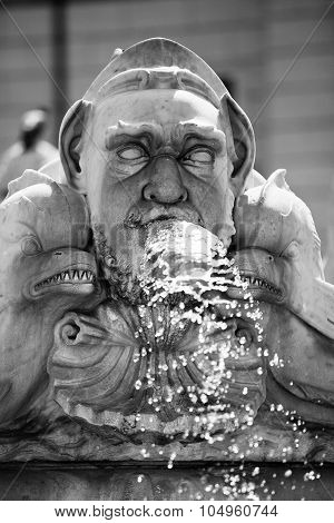 Classical Baroque fountain with a head spewing water Roma Italy