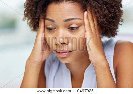 people, emotions, stress and health care concept - unhappy african american young woman touching her head and suffering from headache poster