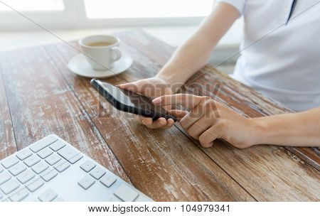 business, technology and people concept - close up of male hand holding smart phone with coffee and keyboard at wooden table