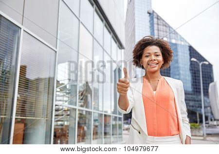 business, gesture and people concept - young smiling african american businesswoman in city showing thumbs u p