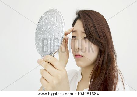 Woman looking at her reflection with worries