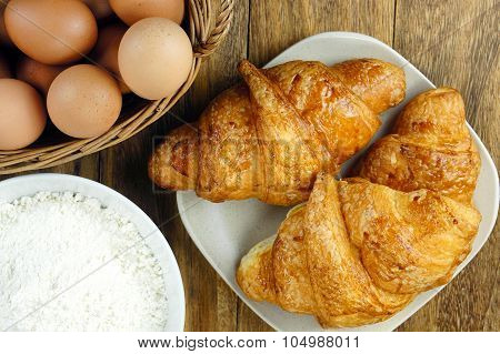Croissant With Eggs And Flour On Rustic Wooden Table