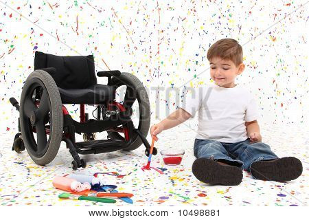 Adorable 2 year old child with wheelchair painting on floor. poster