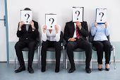 Businesspeople Sitting On Chair Hiding Behind Question Mark Sign poster