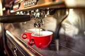 coffee machine preparing fresh coffee and pouring into red cups at restaurant bar or pub. poster