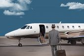 Business man walking toward a private jet poster