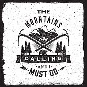 wilderness and nature exploration vintage poster. the mountains are calling and i must go typography concept. artwork for wear with mountains bear ice axes forest trees arrow ribbon. t-shirt design with grunge frame and ink stamp texture poster