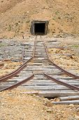 Old rail tracks leading to an abandoned mine shaft in Yukon Territory poster