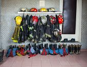 Firefighter suits and gear arranged at fire station poster