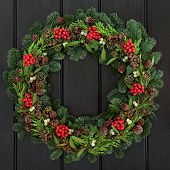 Christmas and winter wreath with holly, mistletoe, pine cones and blue spruce fir over dark blue oak  front door background. poster