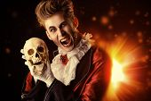 Horrible bloodthirsty vampire holding a skull. Halloween. Dracula costume. poster