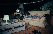 Group of young drunk friends sleeping in a sofa after outdoors party. Fun and alcohol and drugs problems concept. poster