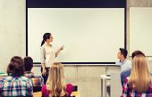 education, high school, technology and people concept - smiling student girl with remote control, laptop computer standing in front of white board and teacher in classroom poster