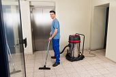Happy Male Worker Cleaning Floor With Vacuum Cleaner Appliance poster