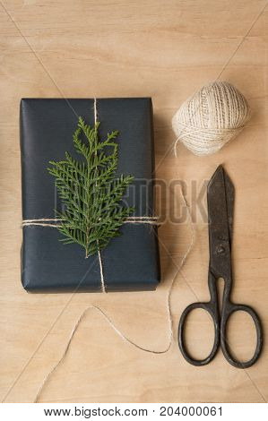 Christmas gift box wrapped in black paper around branch cypress on wooden surface.