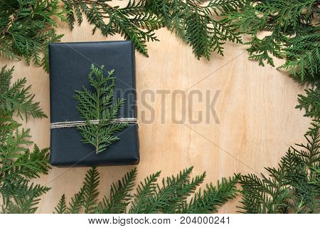 Christmas gift box wrapped in black paper with decor around branch cypress on wooden surface. Rustic style.