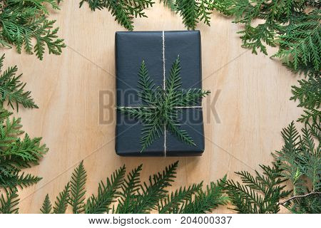 Christmas gift box wrapped in black paper with decor of branch cypress on wooden surface. Copy space. Top view.