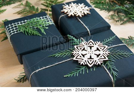 Christmas gift box wrapped in black paper with decor around branch cypress on wooden surface.