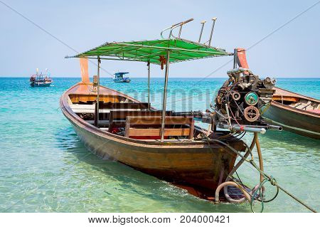 Long boat with engine and tropical beach Andaman Sea Thailand.