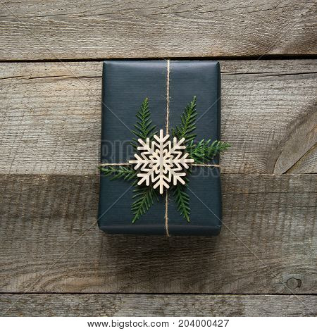 Christmas gift box wrapped in black paper with snowflakes around branch cypress on wooden surface.