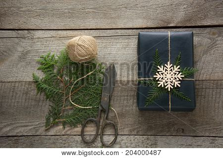 Christmas gift box wrapped in black paper with twine branch cypress on wooden surface. Rustic style.