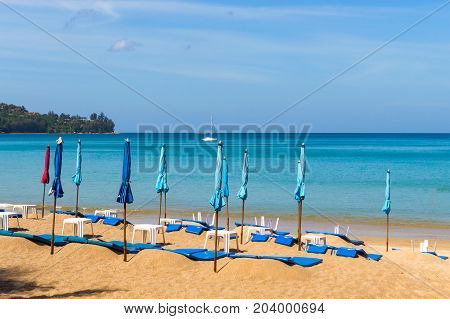 The Low Season At The Seaside. Closed Umbrellas On A Beach With Blue Sea