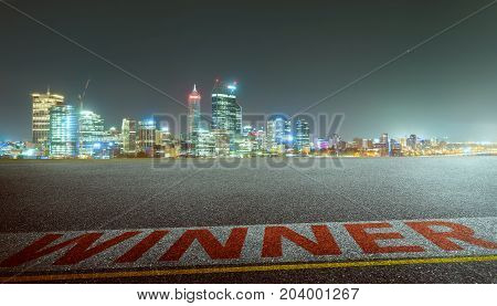 View of the empty asphalt road with winner word and city skyline background . Night scene .