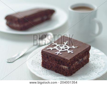 Piece of homemade chocolate cake decorated with sugar snowflake. Chocolate brownies arranged on white plate. Christmas treat. Selective focus on the snowflake.
