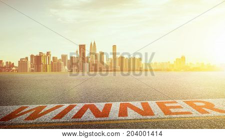 View of the empty asphalt road with winner word and city skyline background . Evening scene .