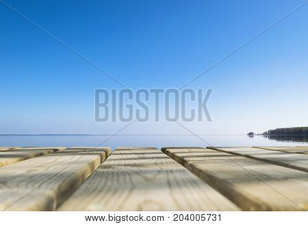 Wooden board empty table in front of blue sea & sky background. Perspective wood floor over sea and sky beach & summer concepts.