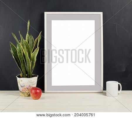 Mock up of blank photo frame with plant pot mug and apple on wooden shelf