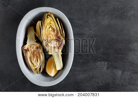 Artichokes and lemons on the plate. This product has one of the highest antioxidant capacities. Traditional vegetables in italian cuisine. Photo contains the copy space